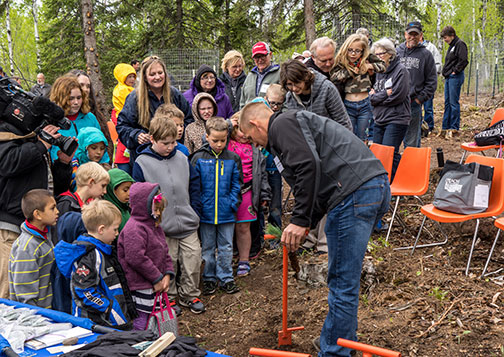 Birch Grove students watch as MP Land Management specialist Corey Skerjance demonstrates how to plant a tree seedling.