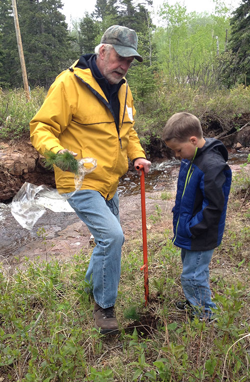 Jack Rajala helps second-grader Silas Ekstrom plant a tree.